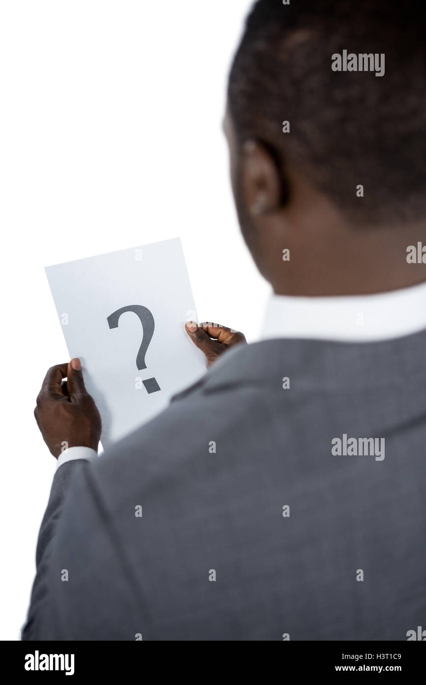 Rear view of businessman holding a question mark sign - Stock Image