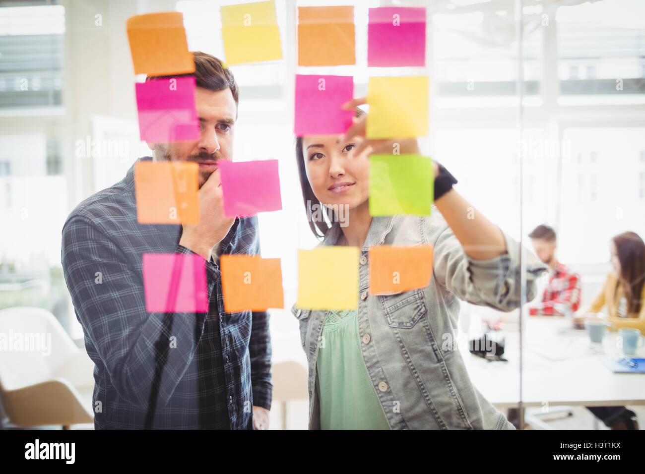 Creative business people looking at multi colored sticky notes on glass - Stock Image