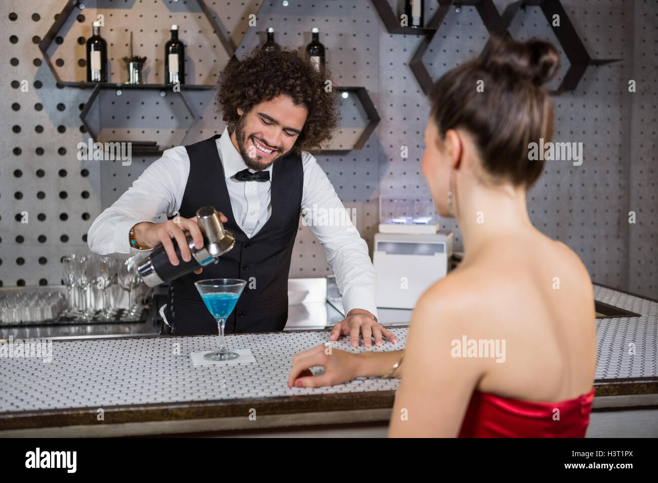 Waiter pouring cocktail in womans glass at bar counter - Stock Image