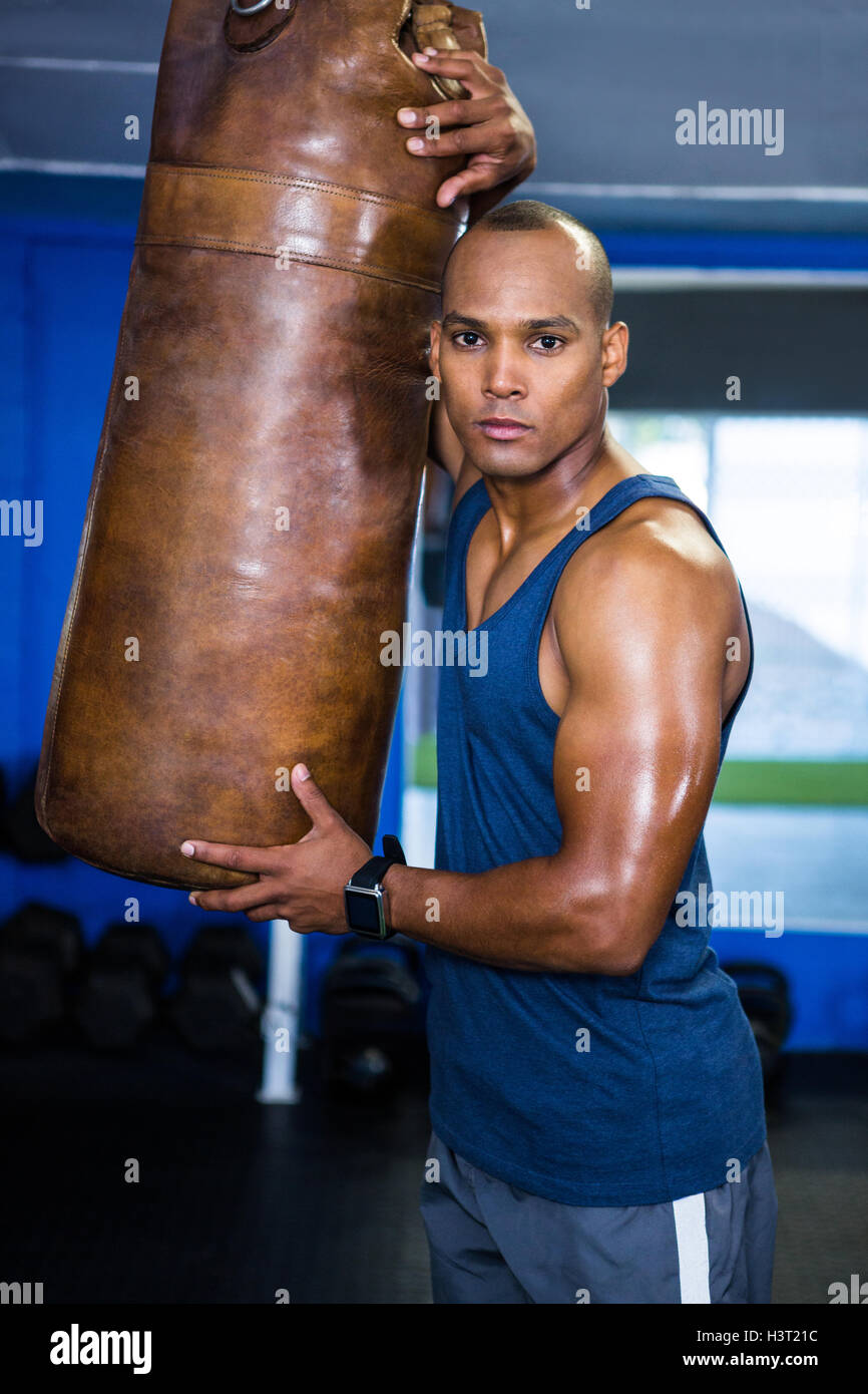 Confident male athlete by punching bag - Stock Image