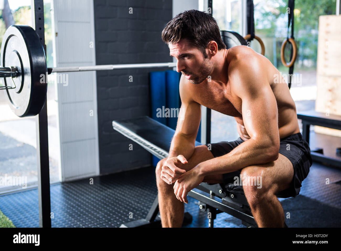 Man sitting on exercise equipment in gym - Stock Image