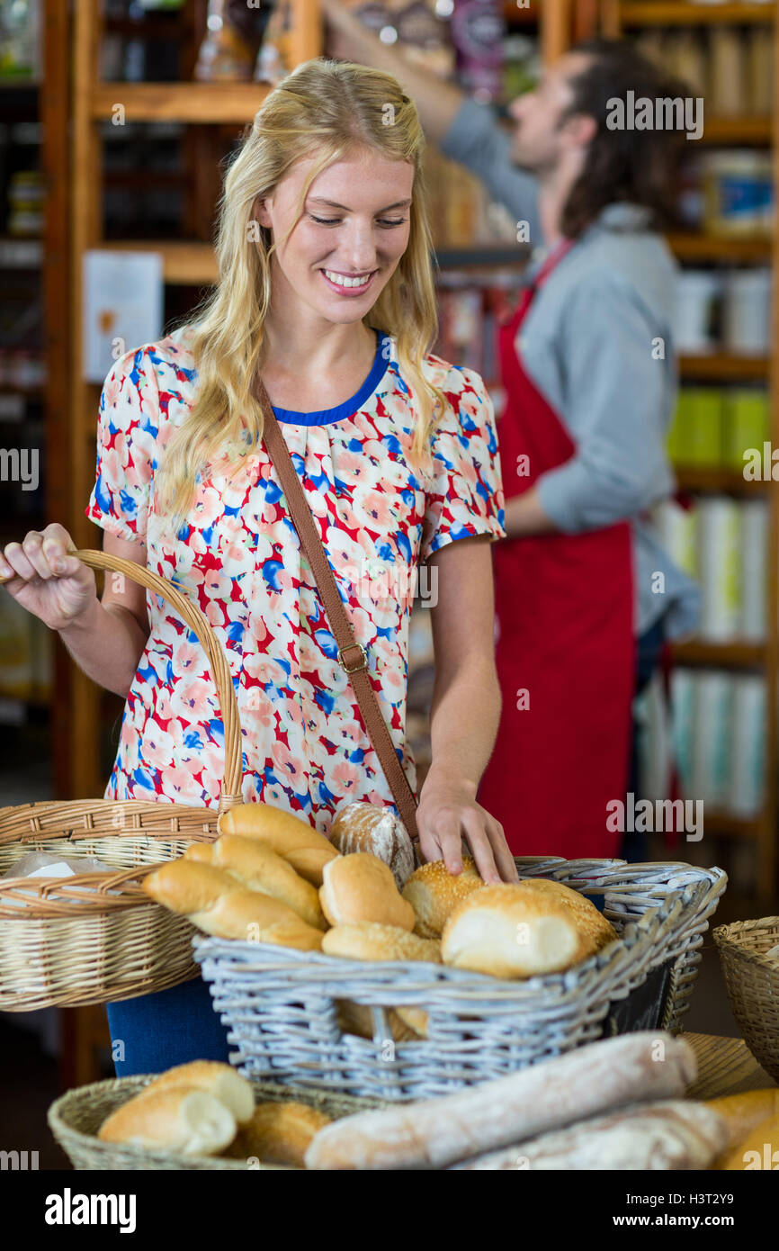 Smiling woman purchasing bread - Stock Image