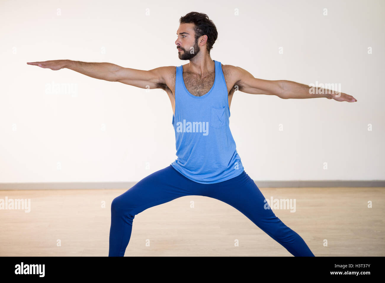 Man performing warrior pose - Stock Image