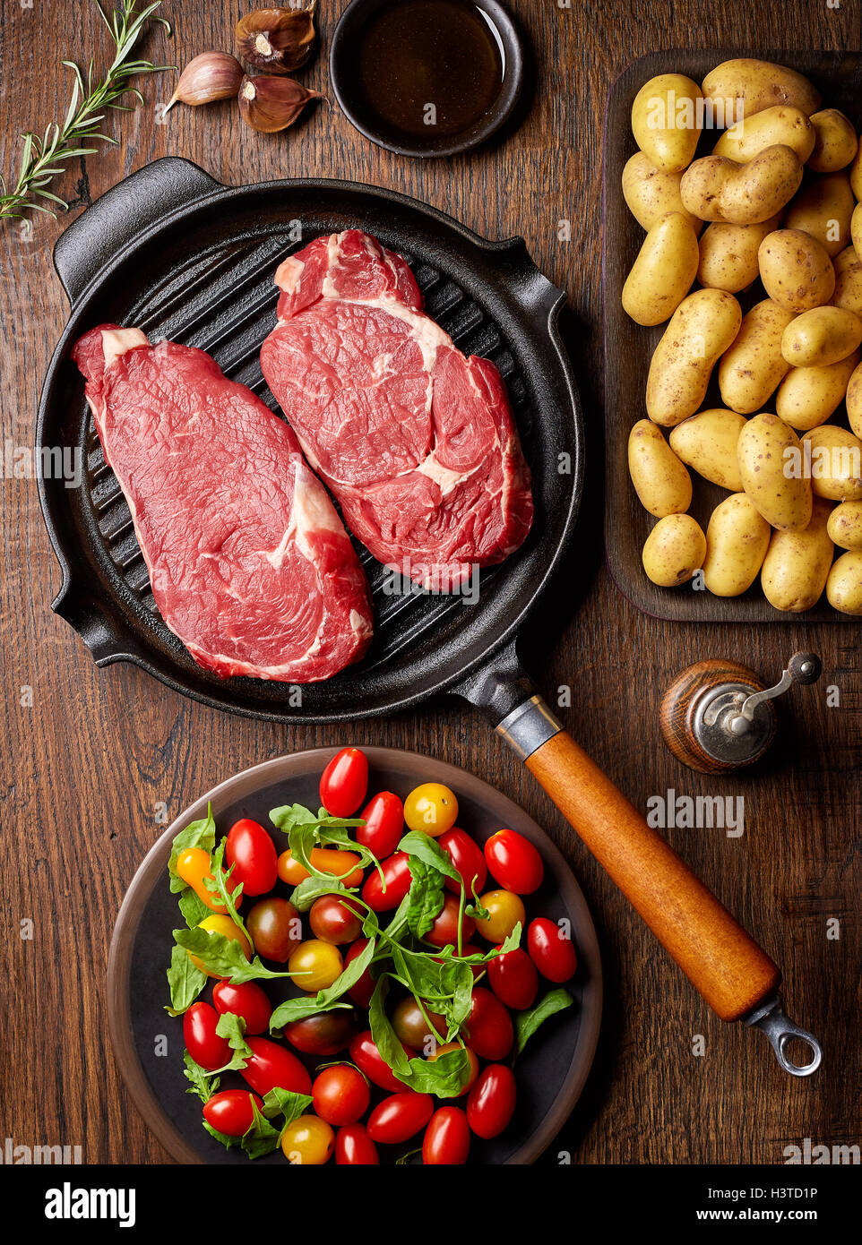 Raw beef steak on grill pan, potatoes, spices and tomatoes, top view, on wooden table - Stock Image