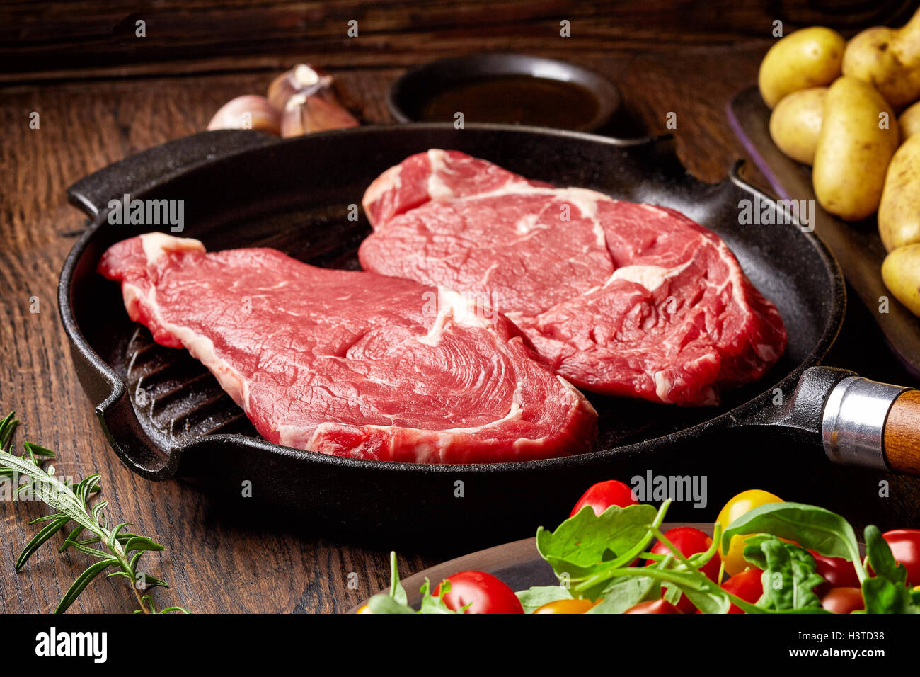 Raw beef steak on grill pan, potatoes, spices and tomatoes on wooden table - Stock Image