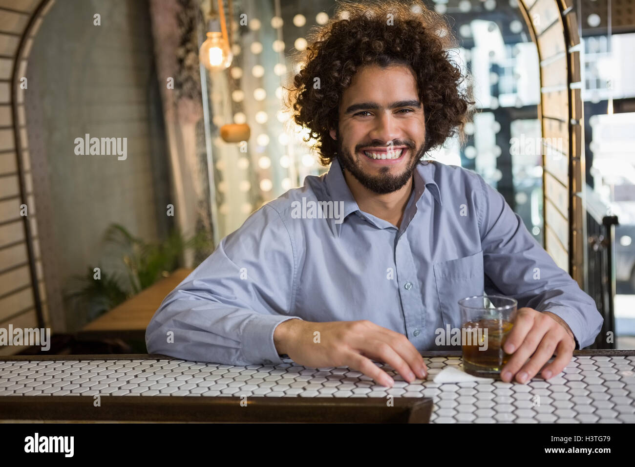 Man sitting on bar counter with glass of whisky - Stock Image