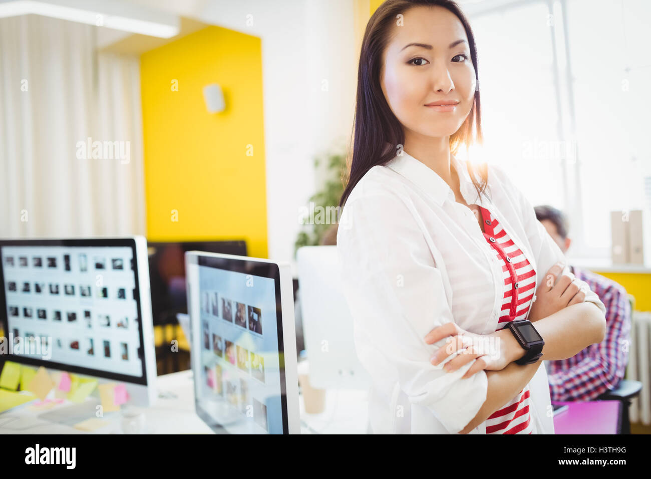Portrait of confident executive standing at editing office - Stock Image