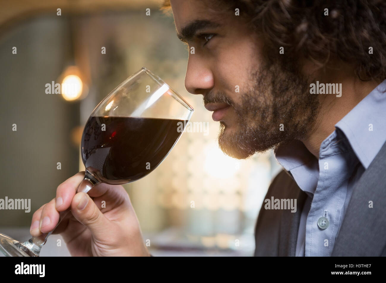 Businessman having glass of red wine - Stock Image