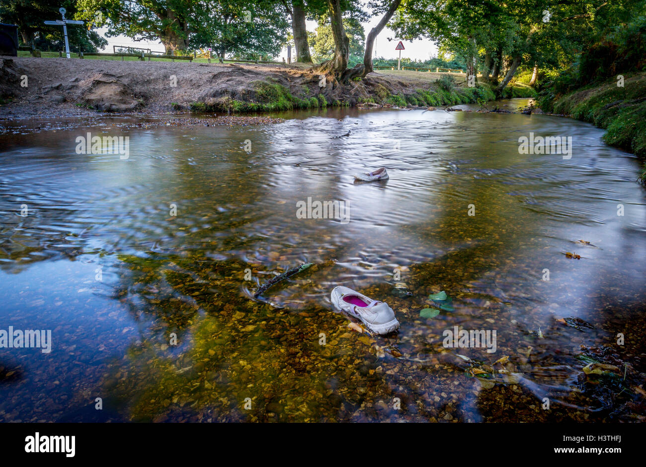 flowing river with forgotten shoes left behind - Stock Image