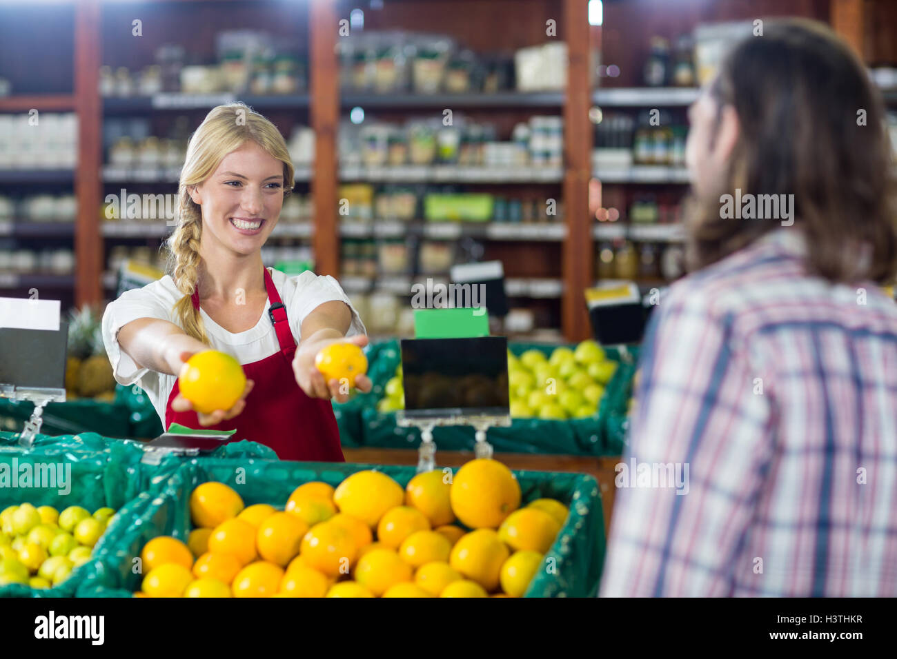 Smiling staff assisting a man with grocery shopping - Stock Image