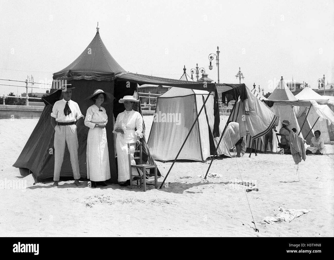 Fashionable people with beach tents at Deauville seaside resort In Normandy France 1912 - Stock Image