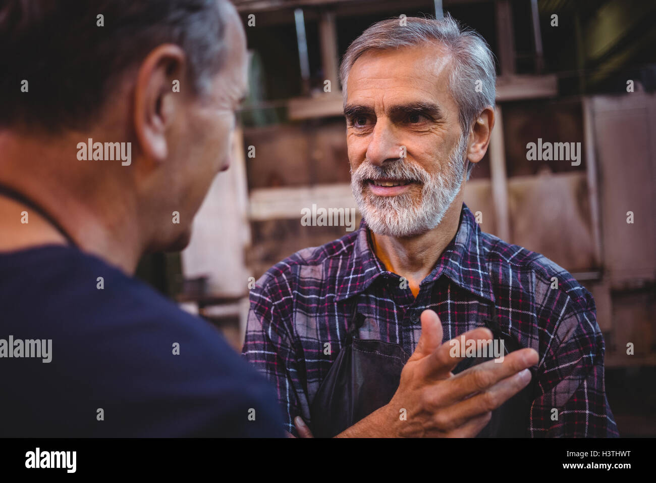 Glass blower interacting with each other - Stock Image