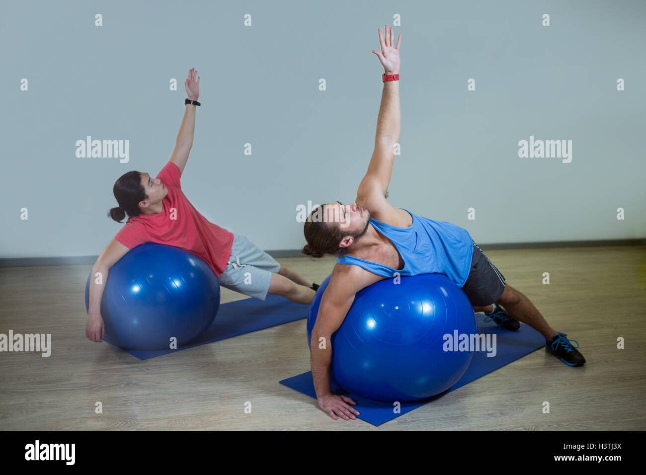 Men exercising with exercise ball - Stock Image