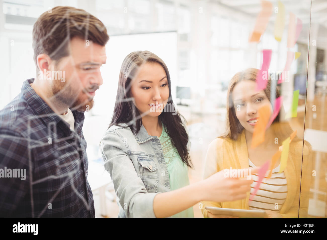Coworkers looking at sticky notes pointed by female photo editor - Stock Image