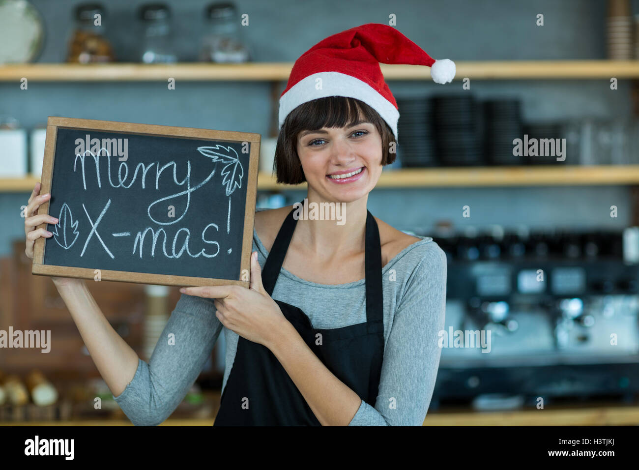 Portrait of waitress showing slate with merry x-mas sign - Stock Image