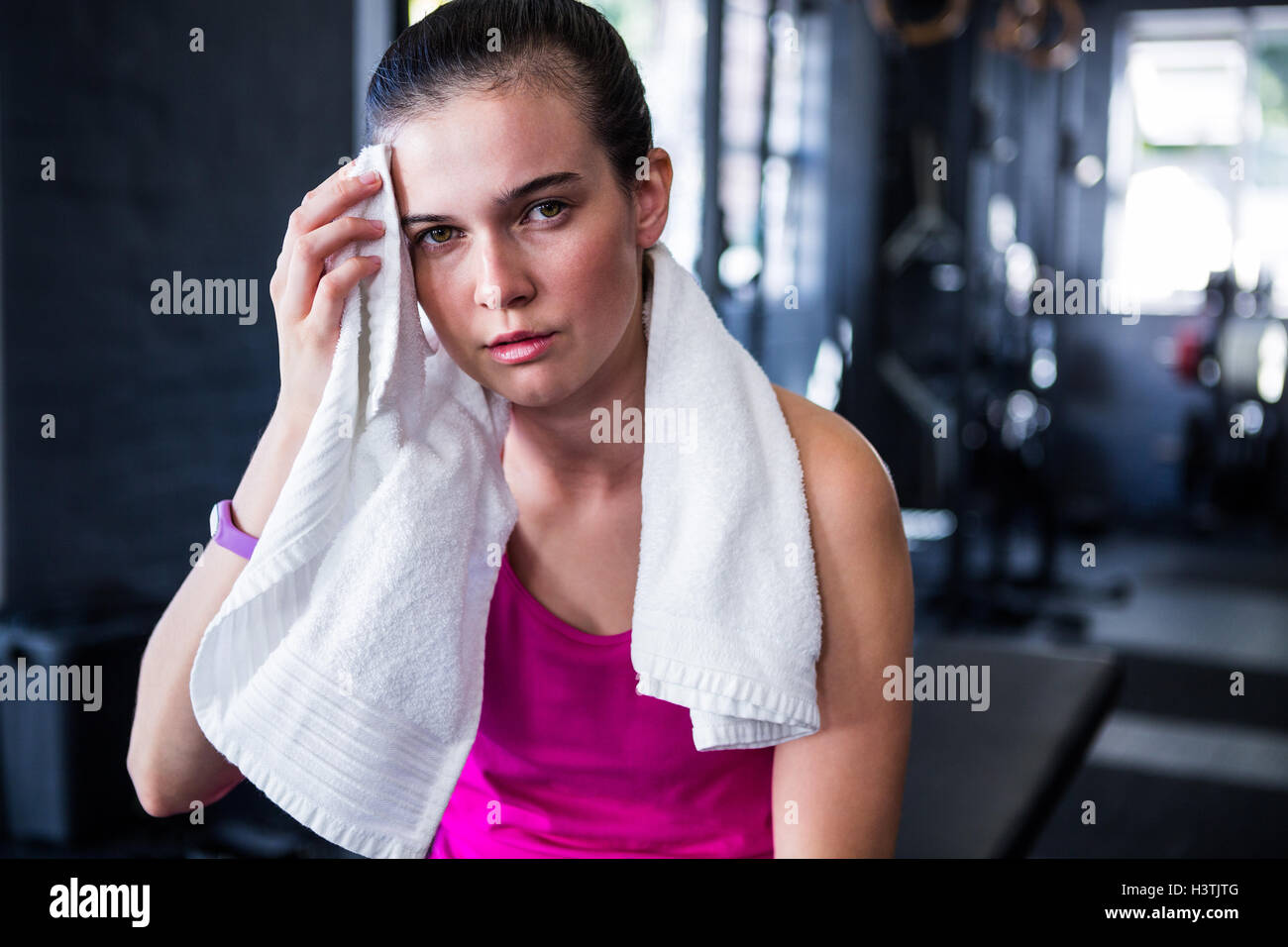 Portrait of young female athlete wiping sweat Stock Photo