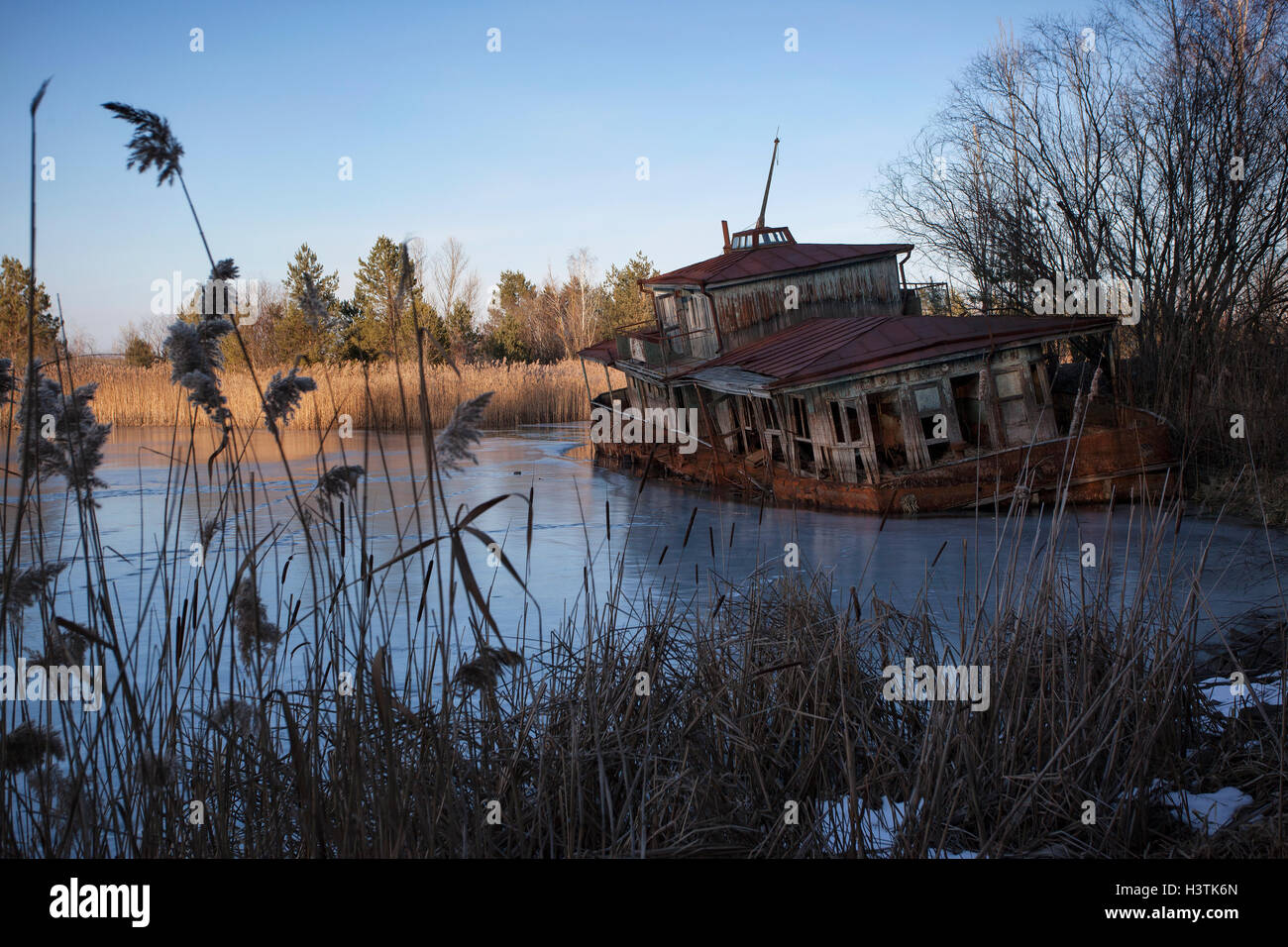 Abandoned shipwreck on the banks of the Pripyat River after the Chernobyl disaster. Pripyat, Chernobyl Exclusion - Stock Image