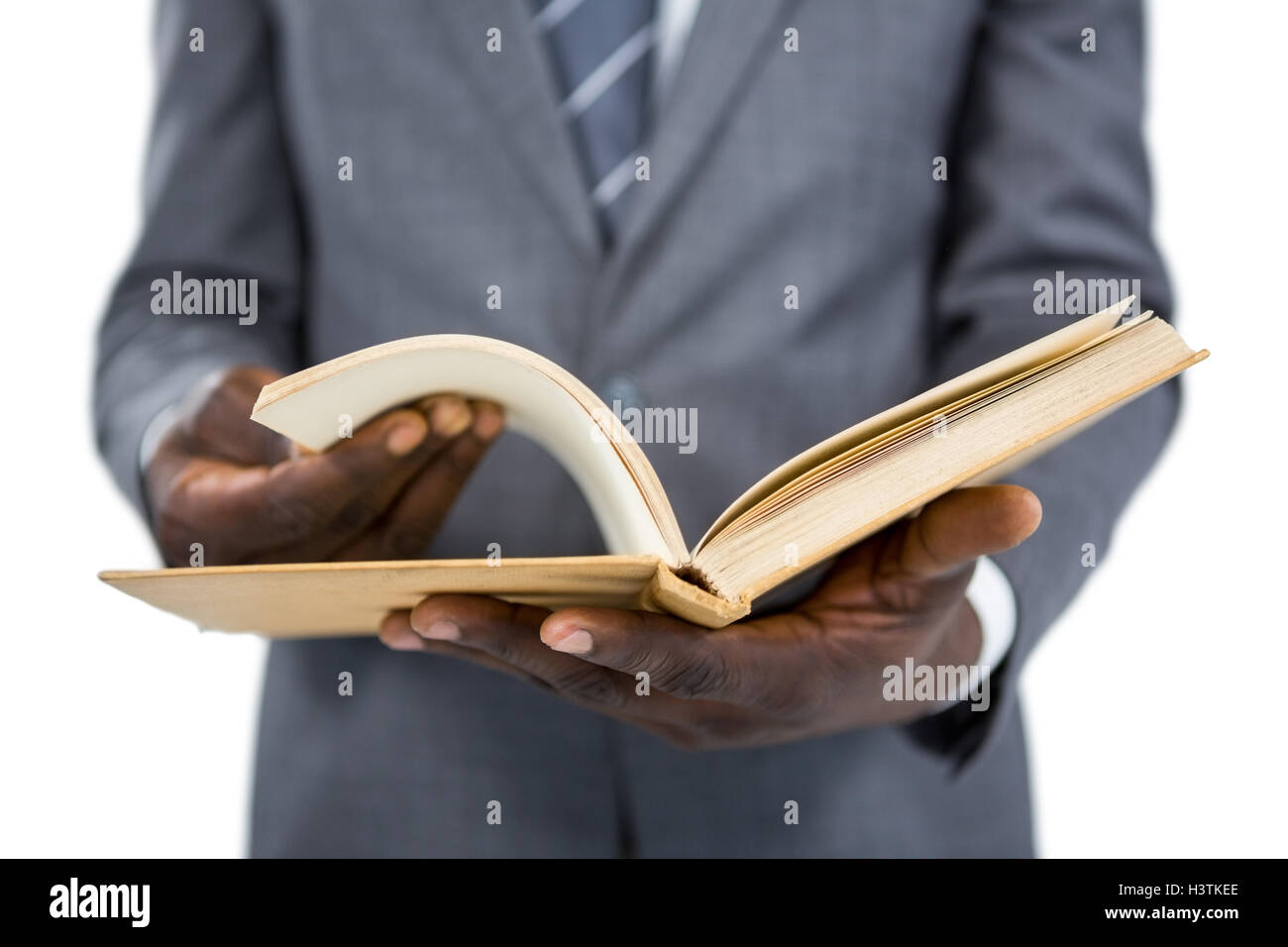 Mid section of businessman flipping the pages of a book - Stock Image