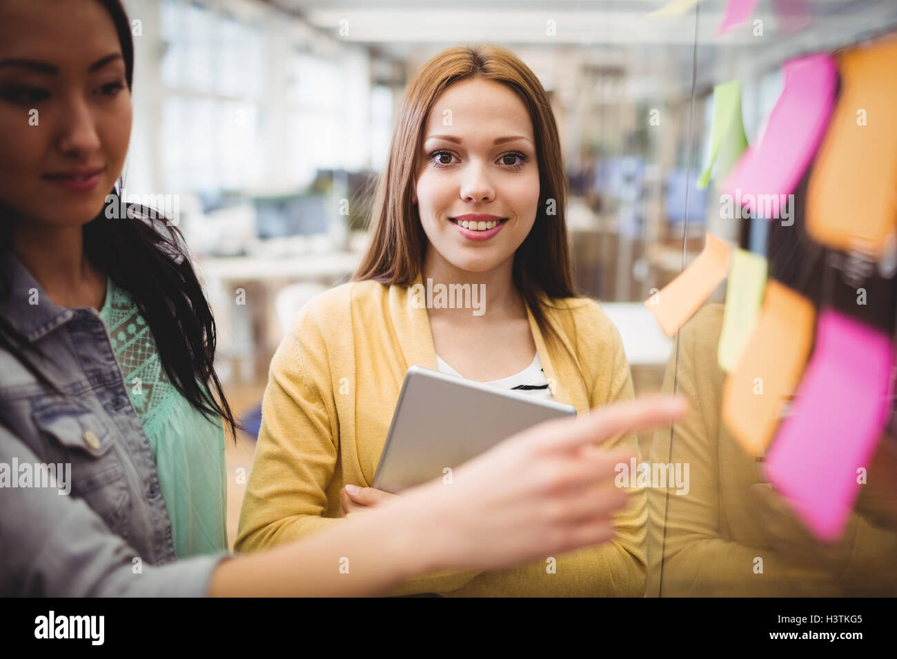 Photo editor standing near female coworkers pointing on sticky note - Stock Image