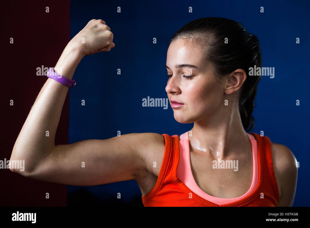 Close-up of woman flexing muscles in gym - Stock Image