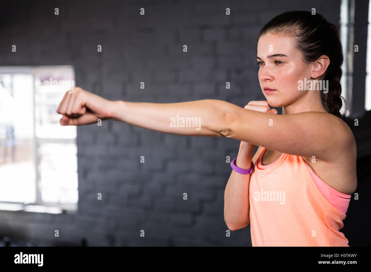 Young woman punching in gym - Stock Image