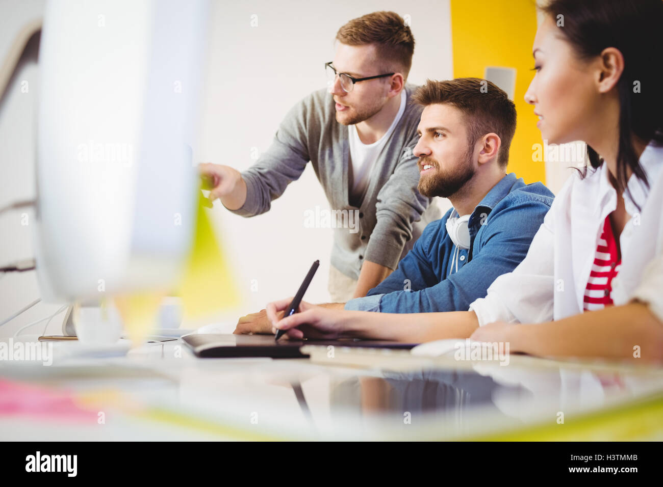 Executive pointing at computer monitor to colleagues in creative office - Stock Image
