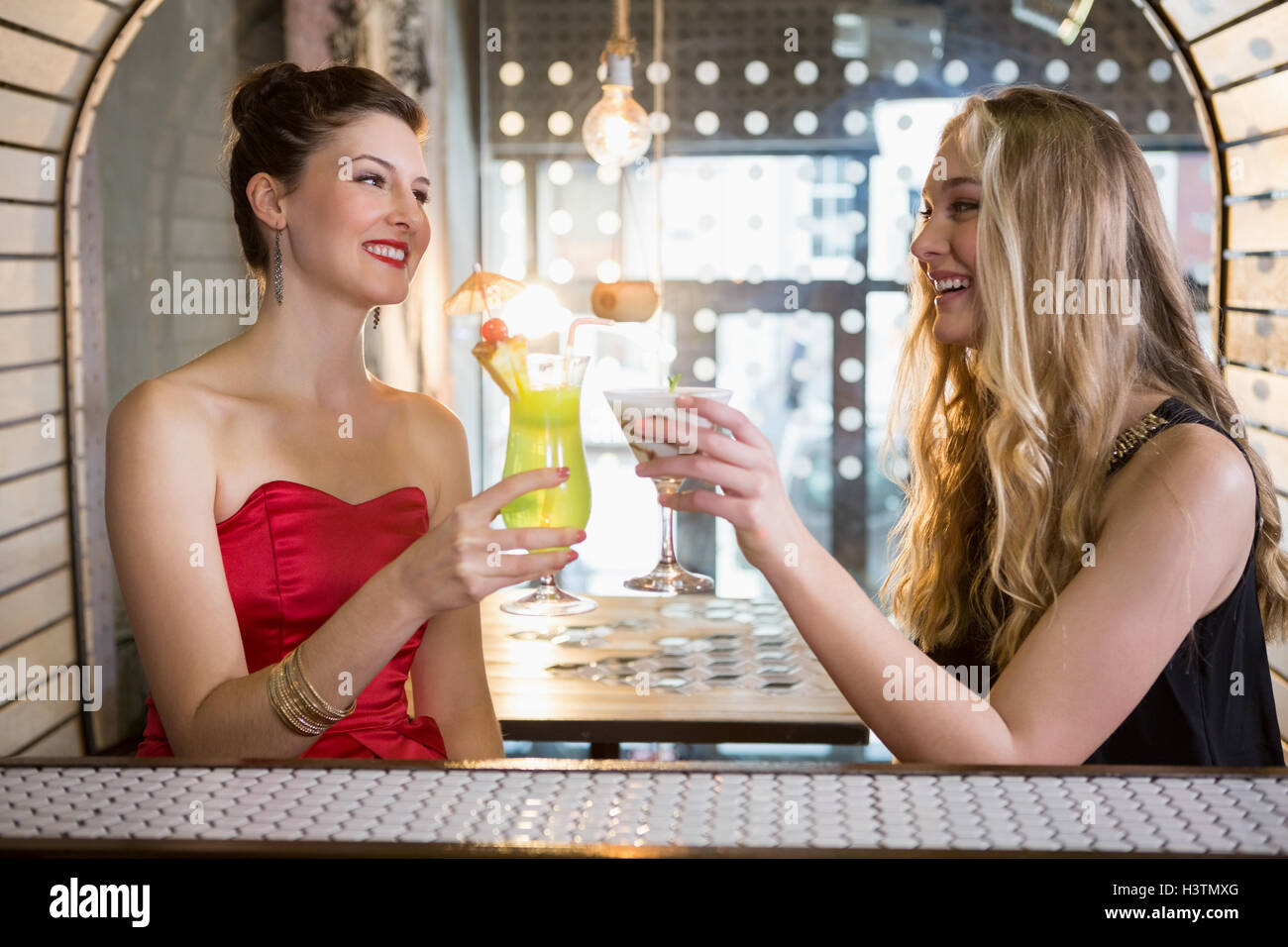 Female friends toasting a glass of cocktail in bar - Stock Image