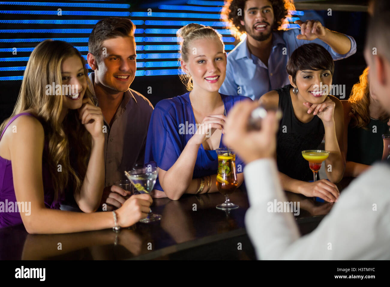 Happy friends standing at bar counter - Stock Image
