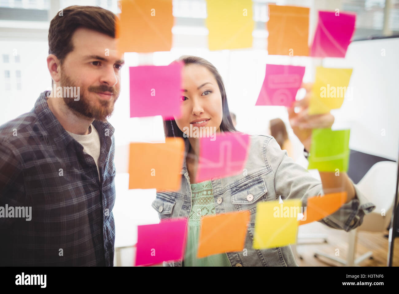 Photo editors looking at multi colored sticky notes on glass Stock Photo