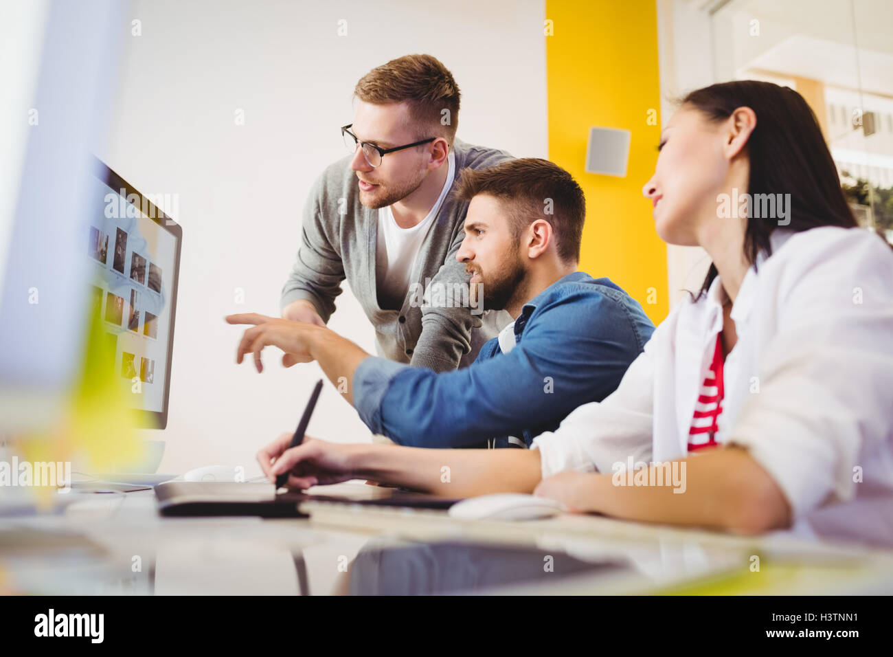 Colleagues discussing photographs at creative office - Stock Image