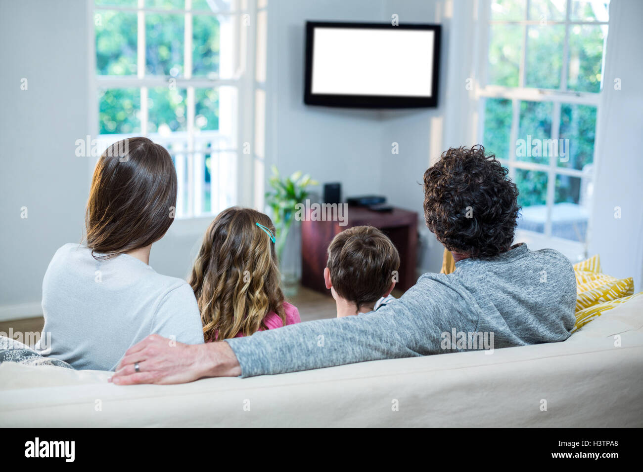 Family watching television while sitting on sofa - Stock Image