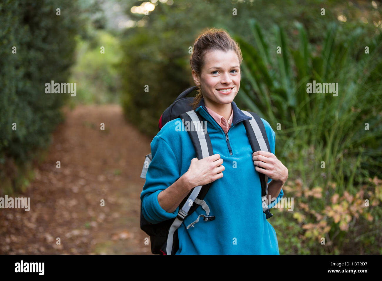 Female hiker standing in forest with backpack - Stock Image