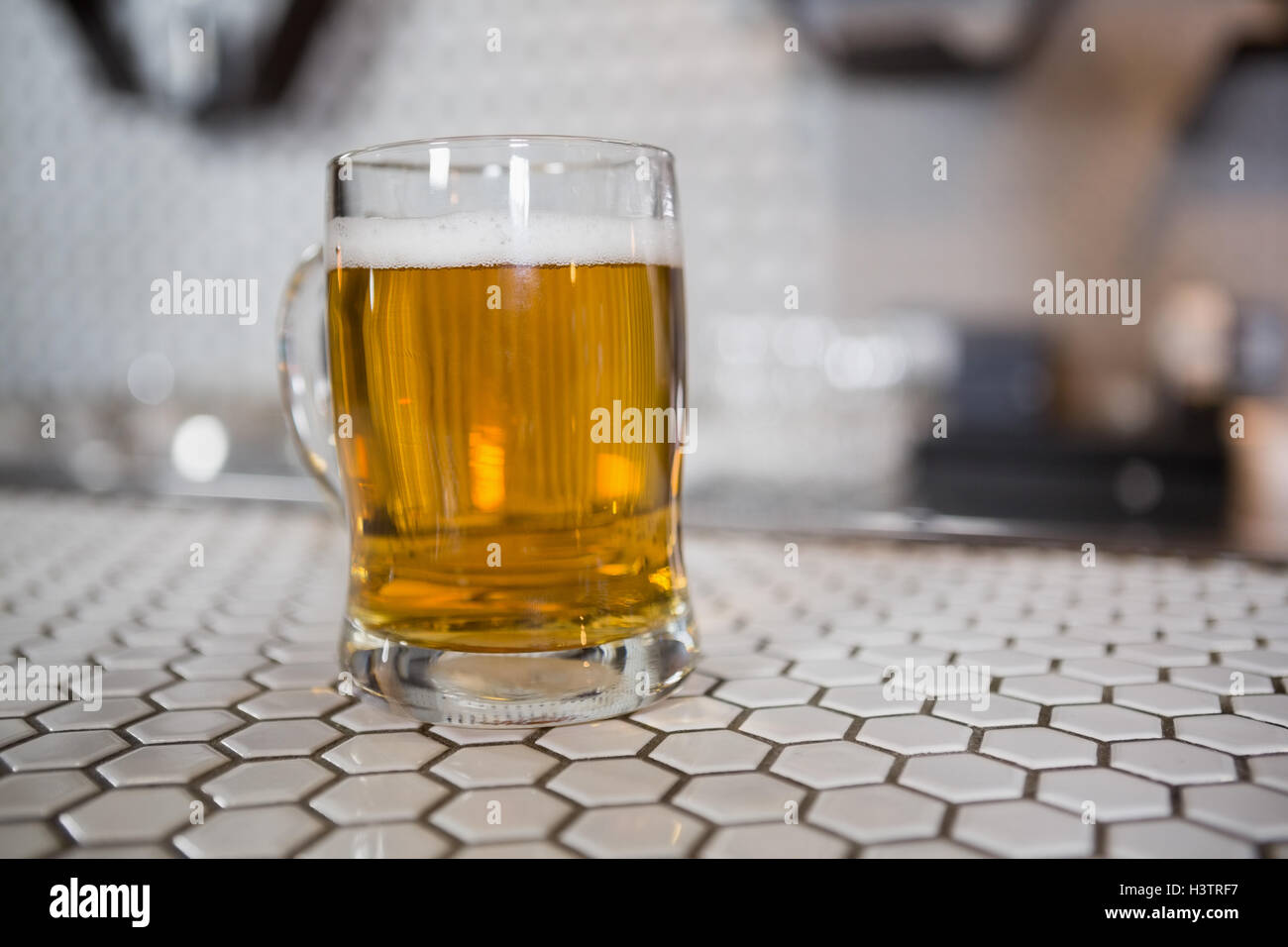 Glass of beer on bar counter - Stock Image