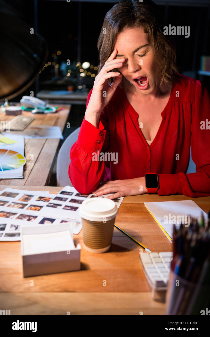 Stressed businesswoman yawning at her desk Stock Photo