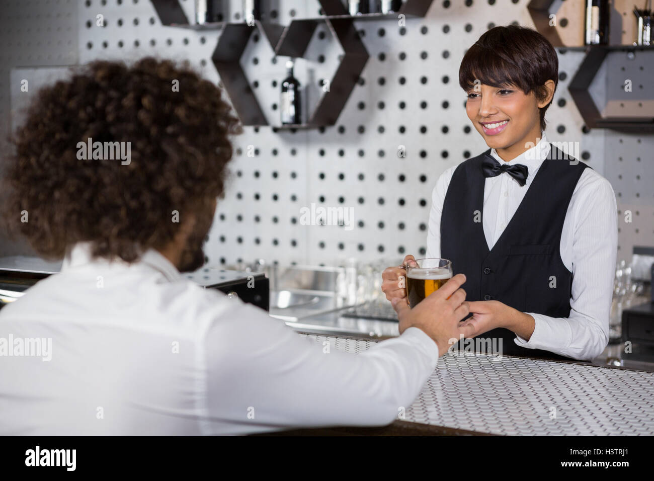 Barmaid serving drink to man - Stock Image