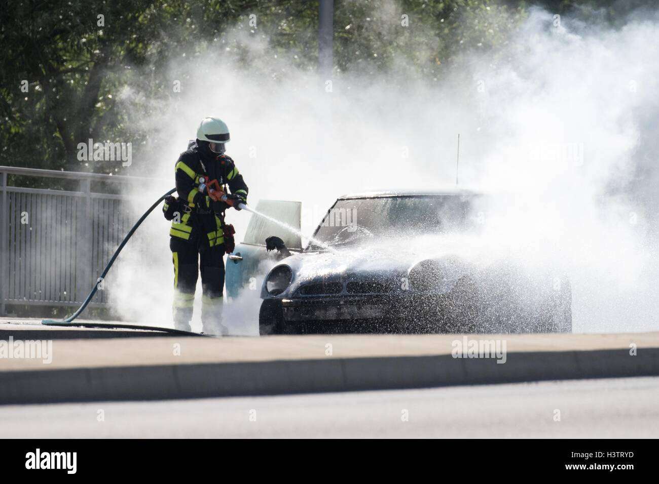 Firefighter extinguishes burning car, Germany - Stock Image