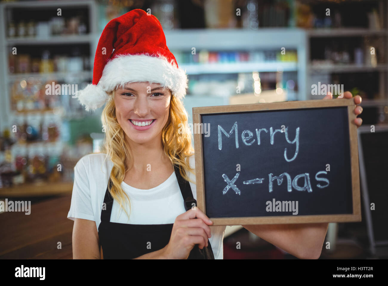 Portrait of waitress showing chalkboard with merry x-mas sign - Stock Image