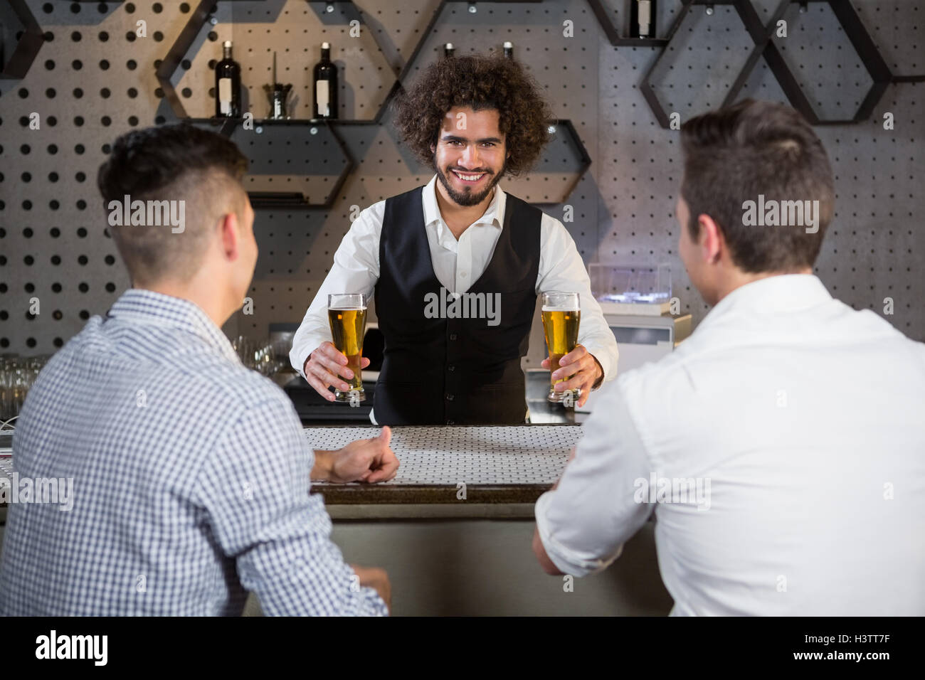 Bartender serving beer to customers - Stock Image