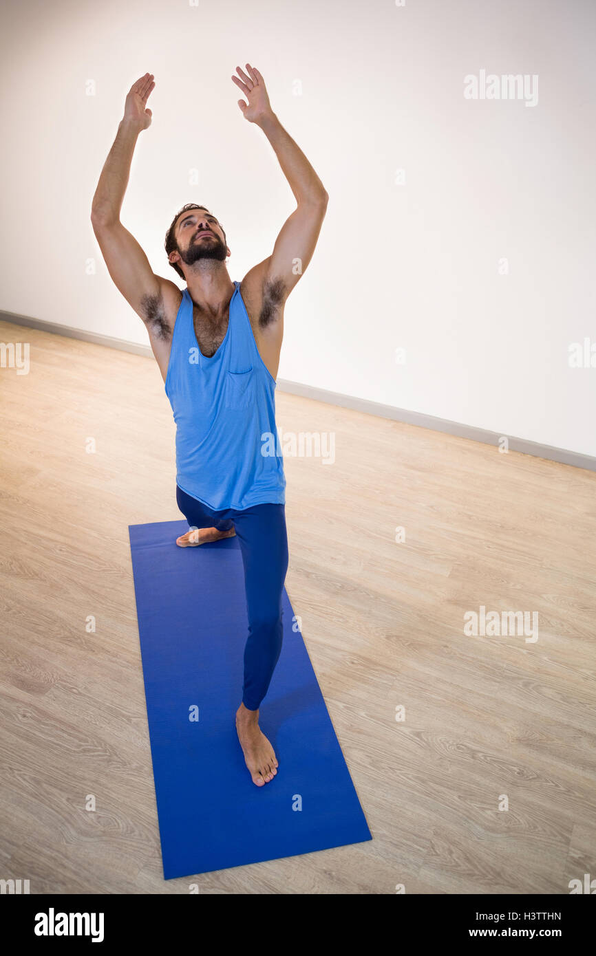 Man doing warrior pose on exercise mat - Stock Image