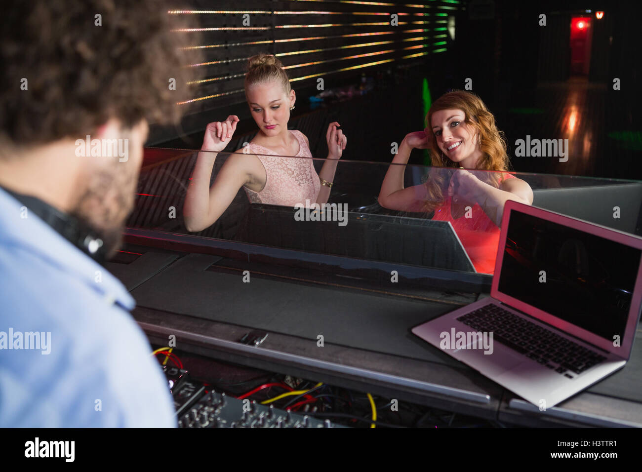 Male disc jockey playing music with two women dancing on the dance floor - Stock Image