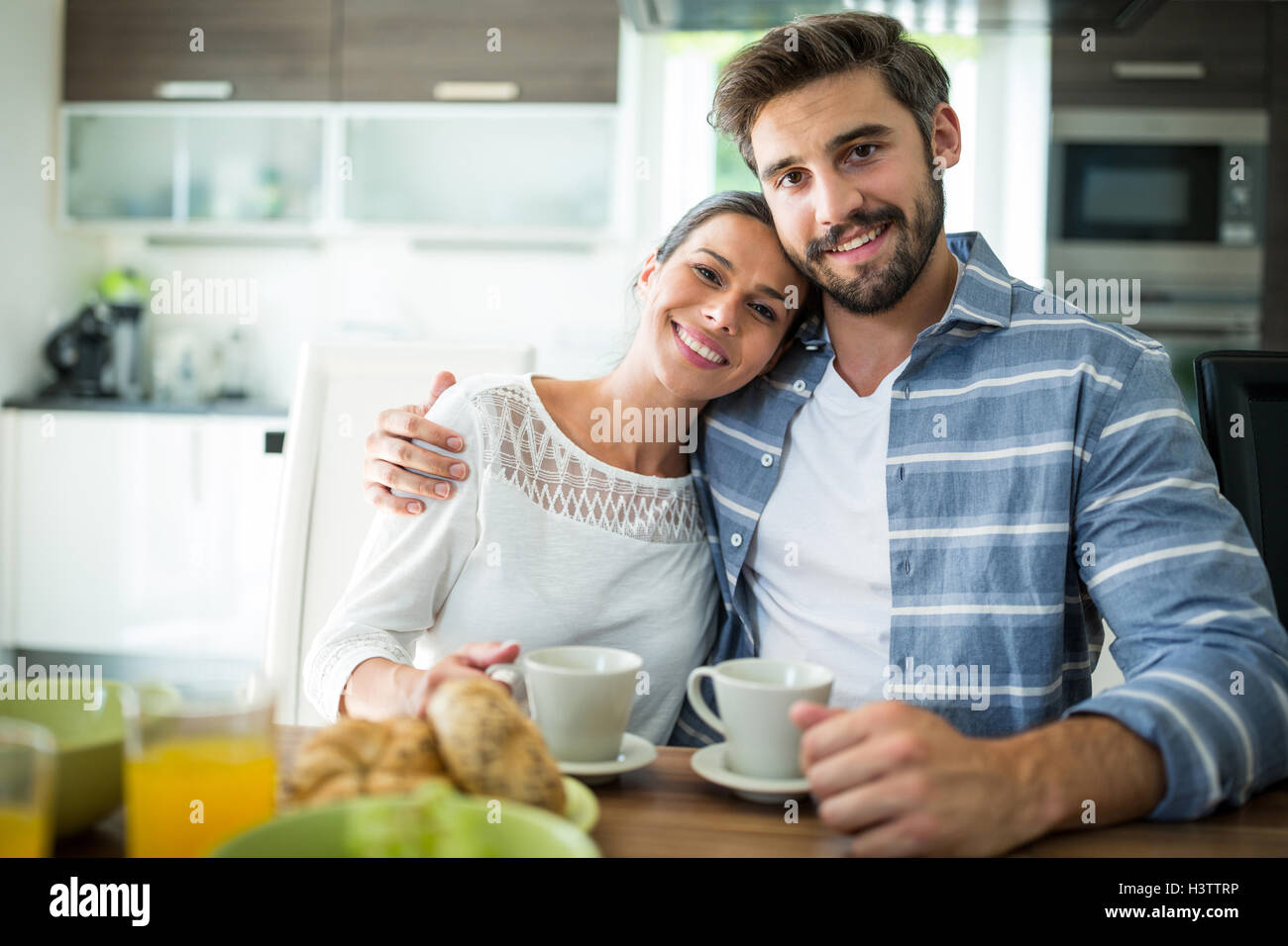 Portrait of couple sitting with arm around while having breakfast - Stock Image