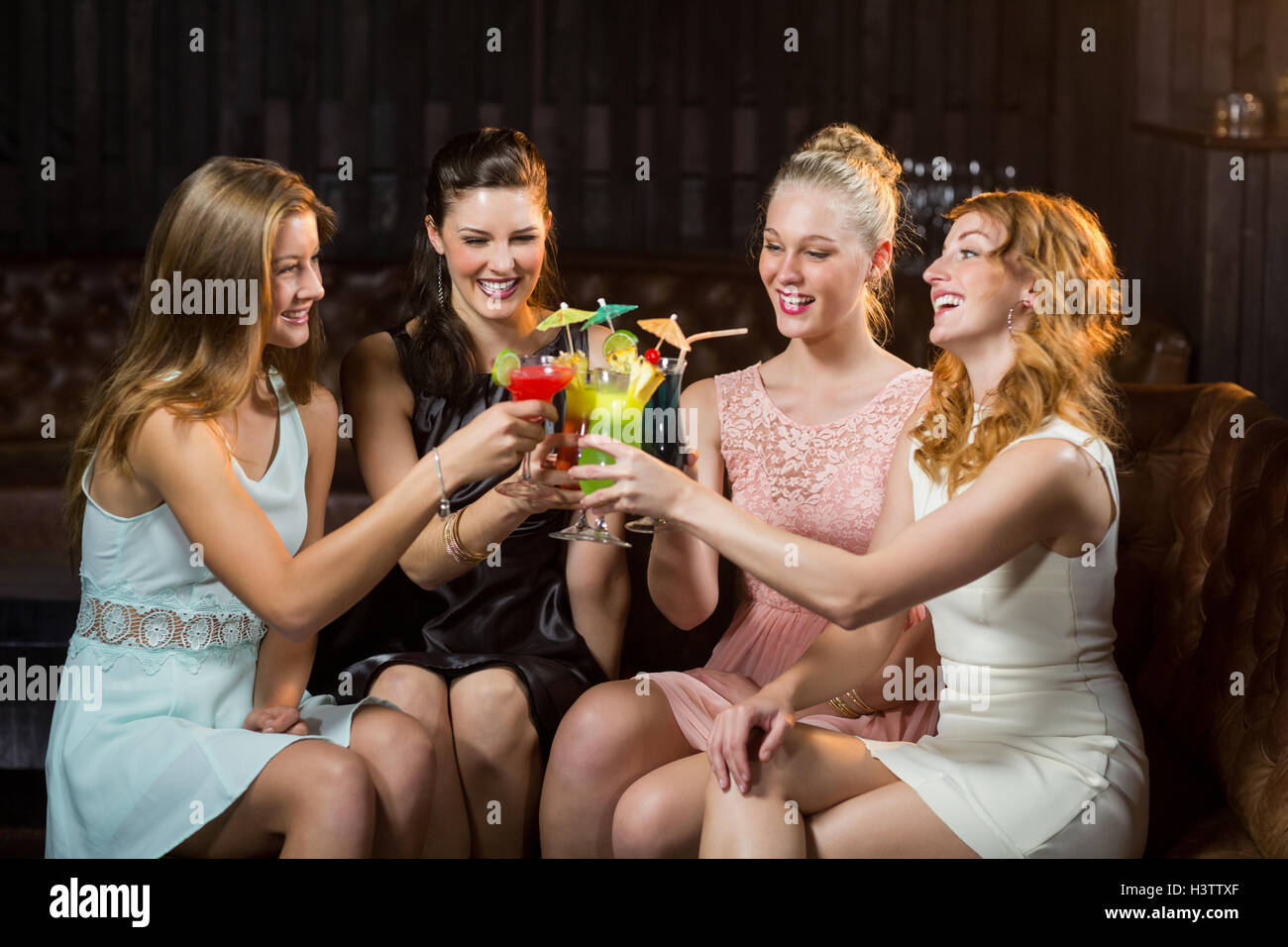 Female friends toasting glasses of cocktail in bar Stock Photo