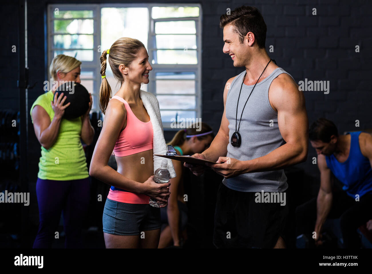 Woman talking with trainer in gym Stock Photo