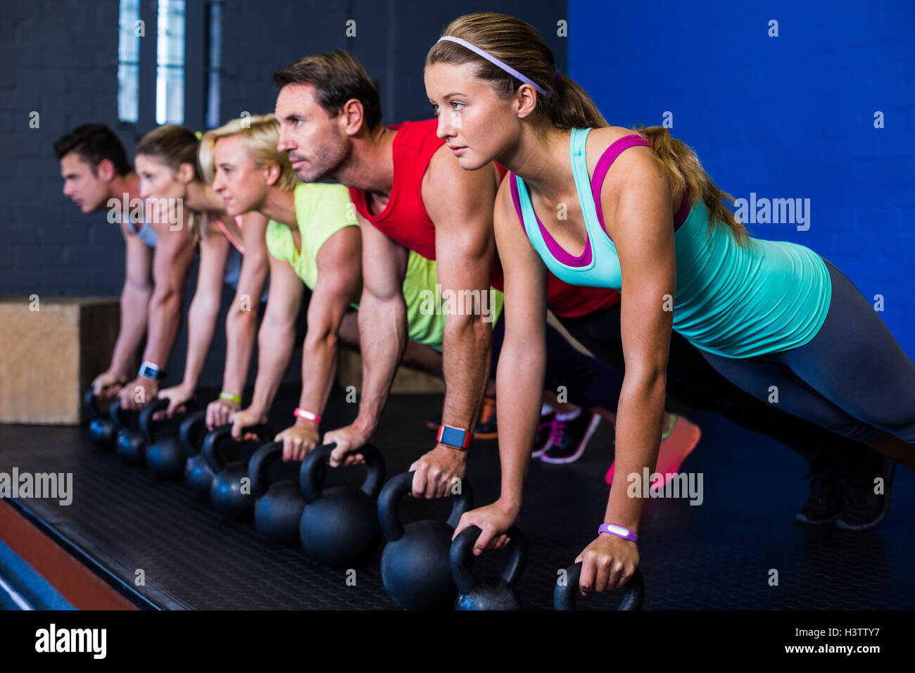 Athletes exercising with kettlebells - Stock Image