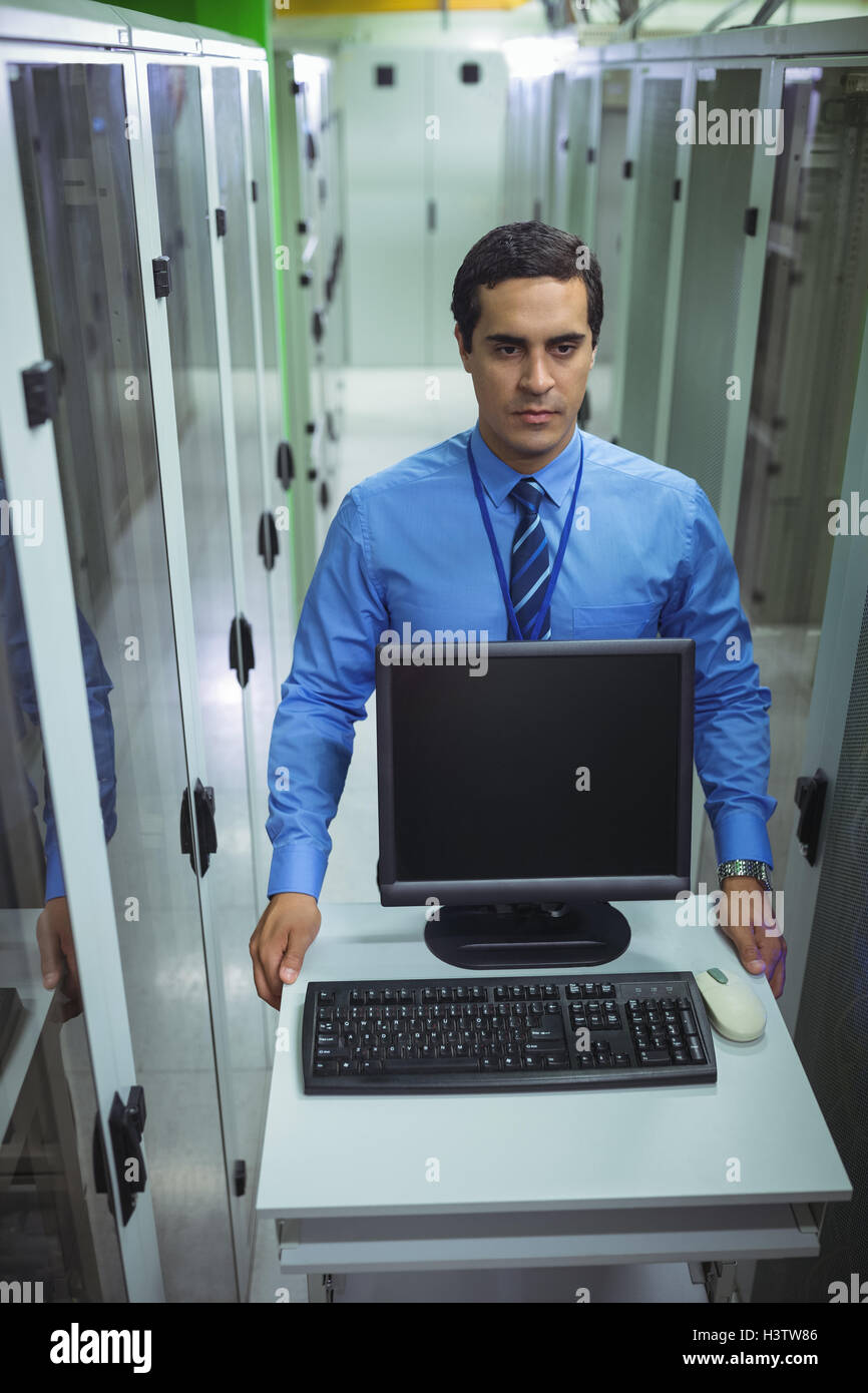 Technician walking with personal computer in hallway - Stock Image