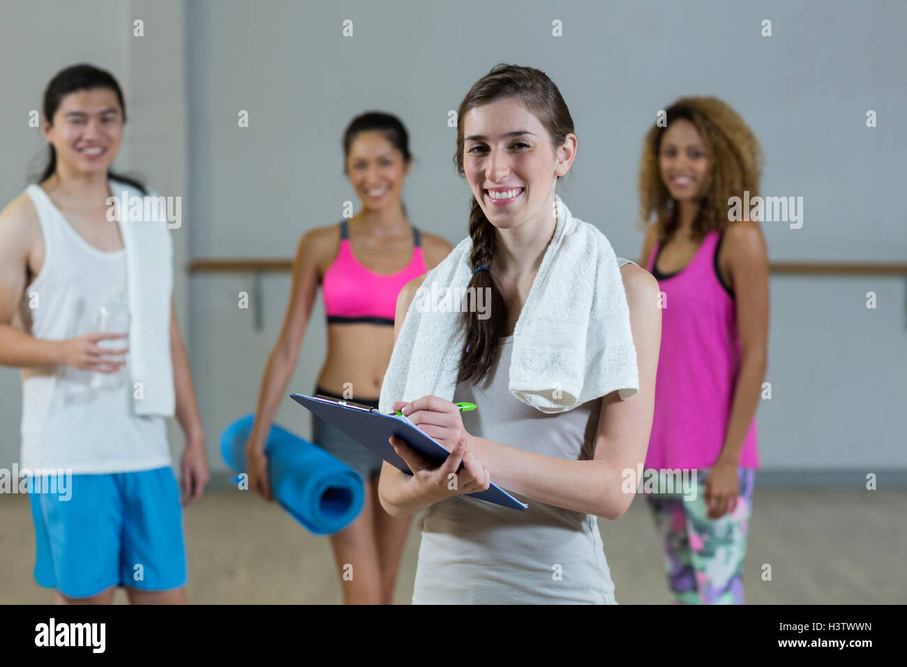 Portrait of female trainer holding clipboard with fitness class in background - Stock Image