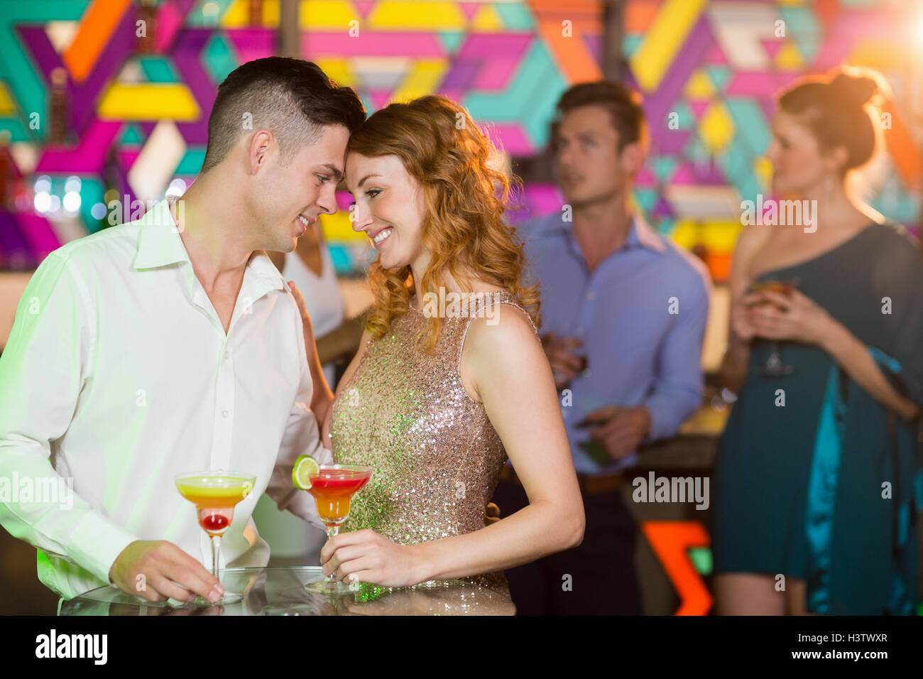 Romantic couple having glass of cocktail - Stock Image
