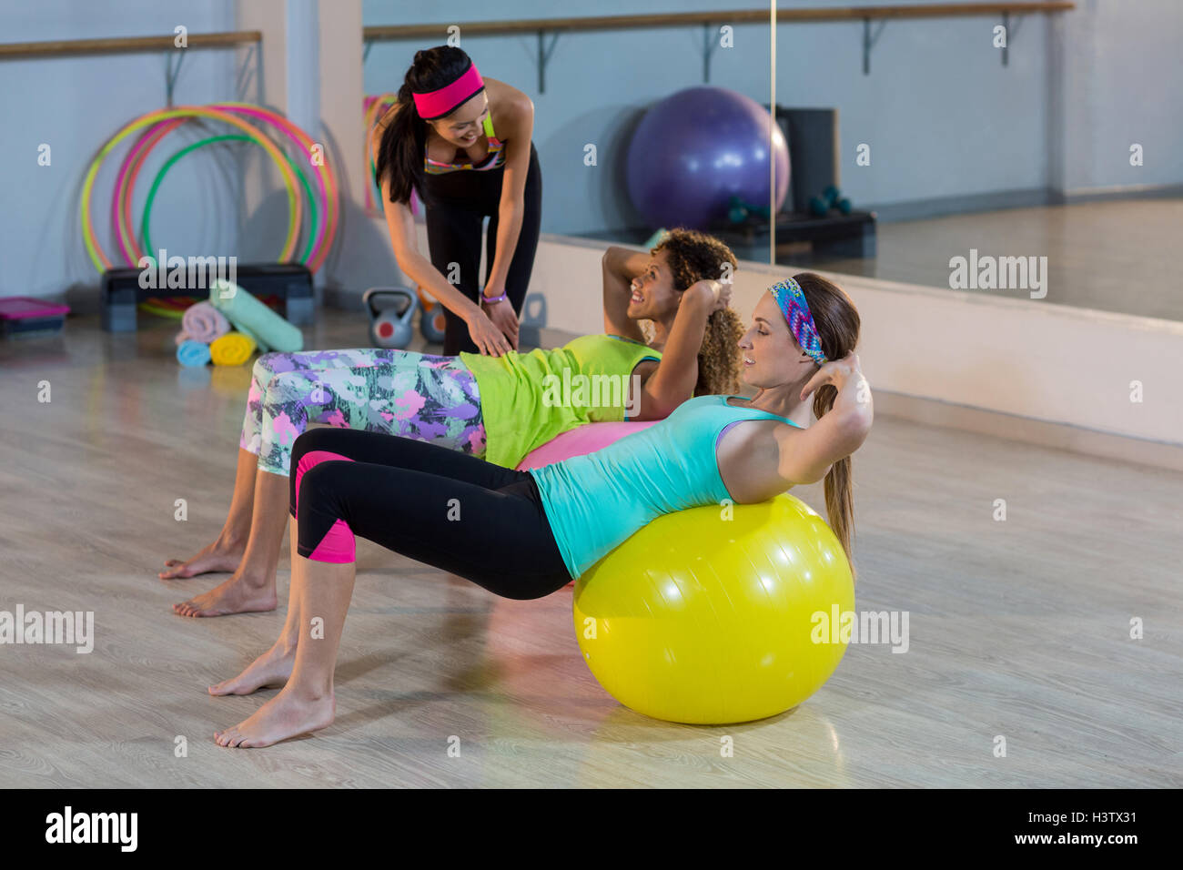 Female trainer assisting woman to exercise on exercise ball - Stock Image