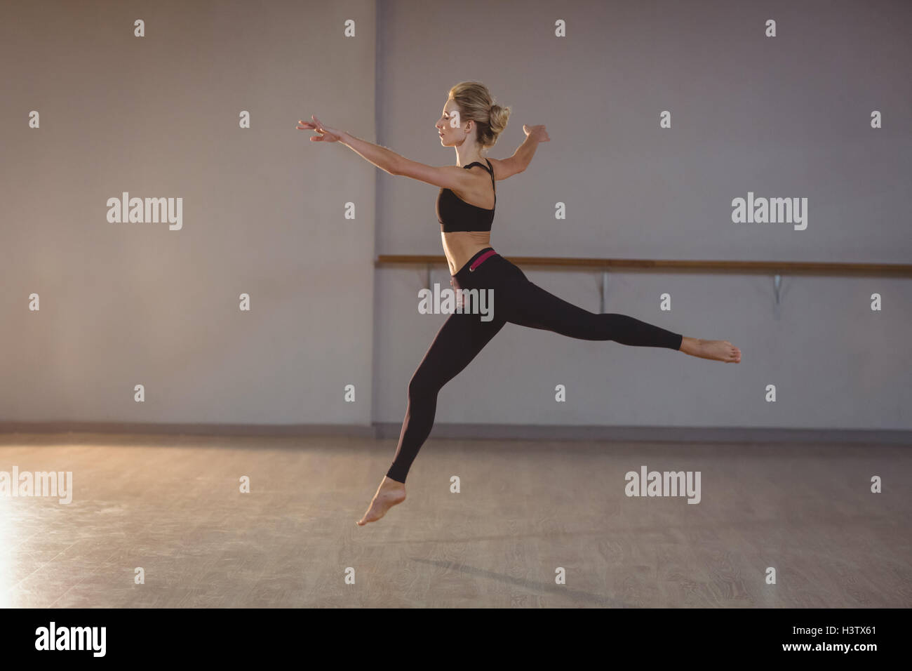 Woman leaping while performing stretching exercise - Stock Image