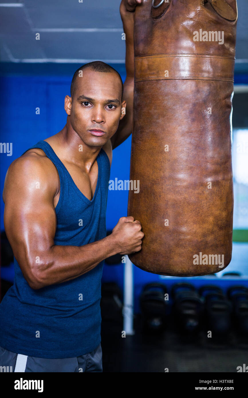 Determined young man standing by punching bag - Stock Image